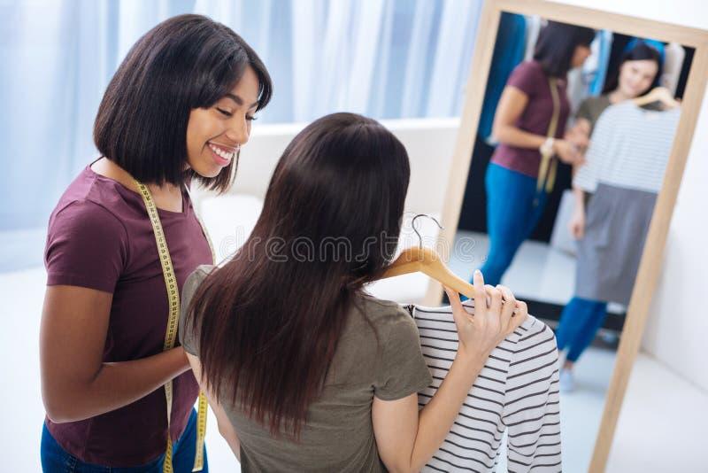 Positiv skräddare som ler, medan se hennes tillfredsställda klient arkivfoto