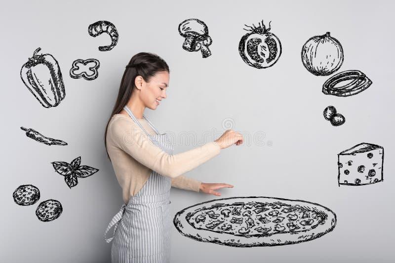 Positiv student som står ensam, medan laga mat pizza royaltyfri foto