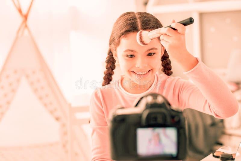 Positiv trevlig flicka som rymmer en yrkesmässig borste arkivbilder