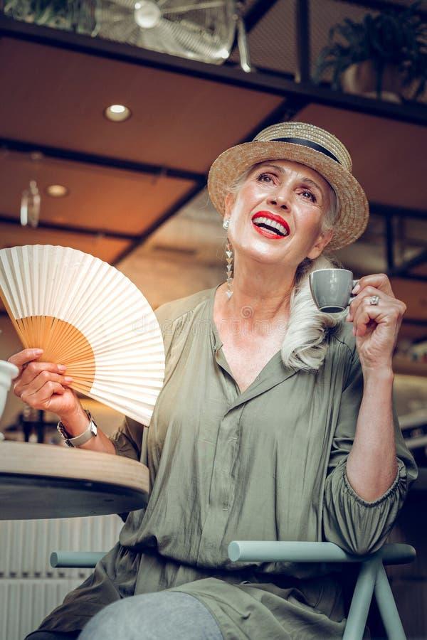 Positiv trevlig kvinna som använder en härlig fan arkivfoto