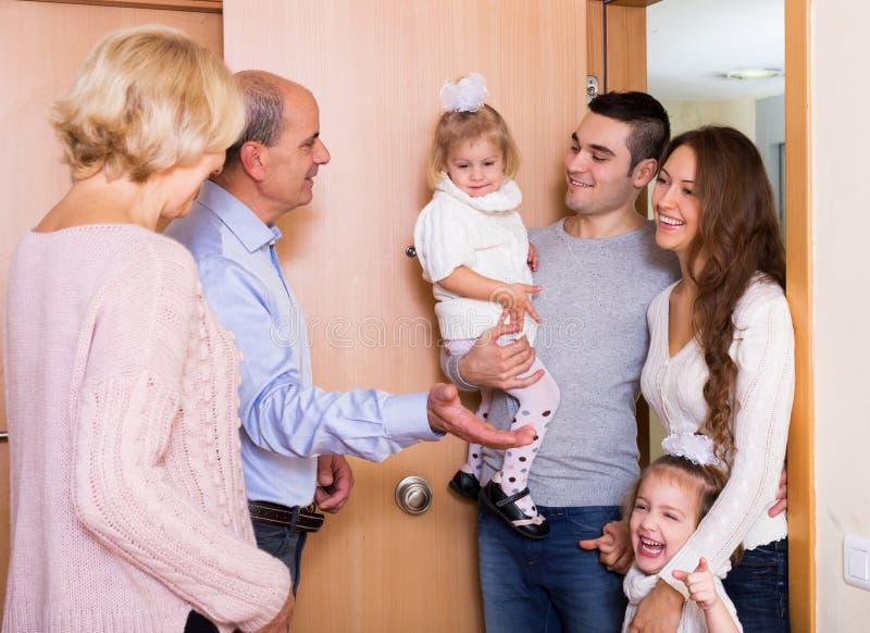 Positiv ung familj som besöker tusen dollarföräldrar arkivbild