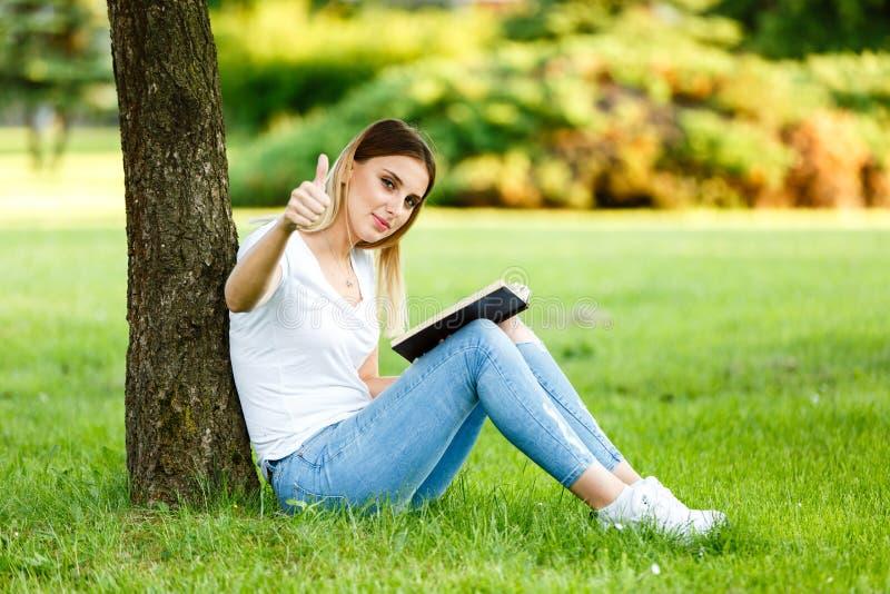 Positiv ung flicka under de tre visande tummarna upp och readin arkivfoto