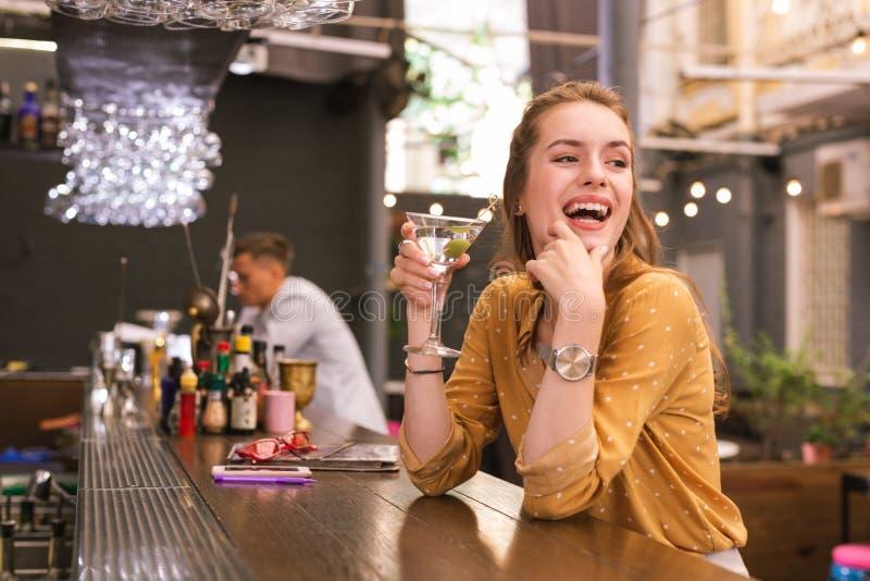 Positiv ung kvinna som skrattar, medan sitta i stången royaltyfri foto