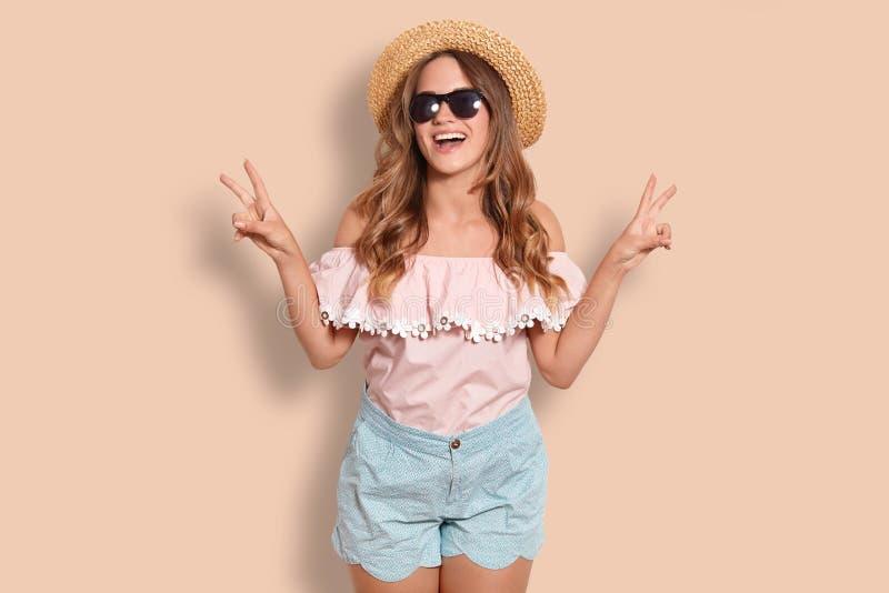Positiv ung kvinnlig turist med glat uttryck, gester med båda händer, den iklädda trendiga sugrörhatten, blusen och kortslutning royaltyfria foton