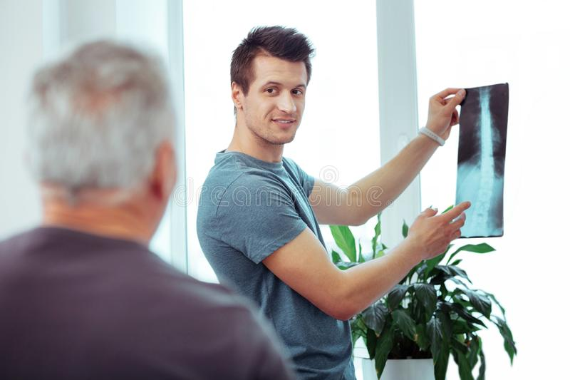 Positiv ung man som visar en bild f?r str?le X royaltyfri fotografi