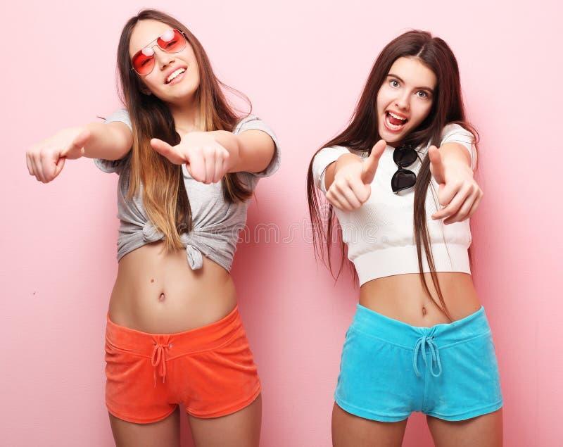 Positiv vänstående av två lyckliga flickor - roliga framsidor, emo fotografering för bildbyråer