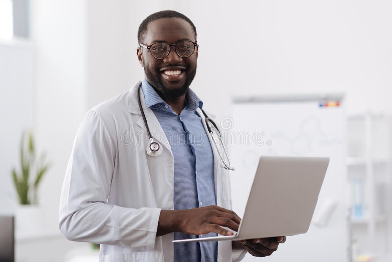 Positiv yrkesmässig doktor som arbetar på bärbara datorn royaltyfria foton
