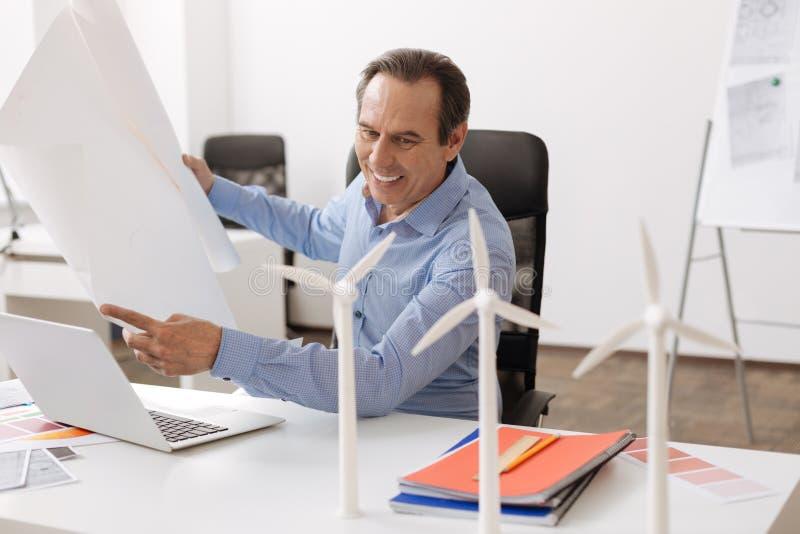 Positiv yrkesmässig tekniker som arbetar med ritningen fotografering för bildbyråer