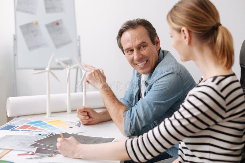 Positiv yrkesmässig tekniker som diskuterar arbetsfrågor med hans kollega arkivbild