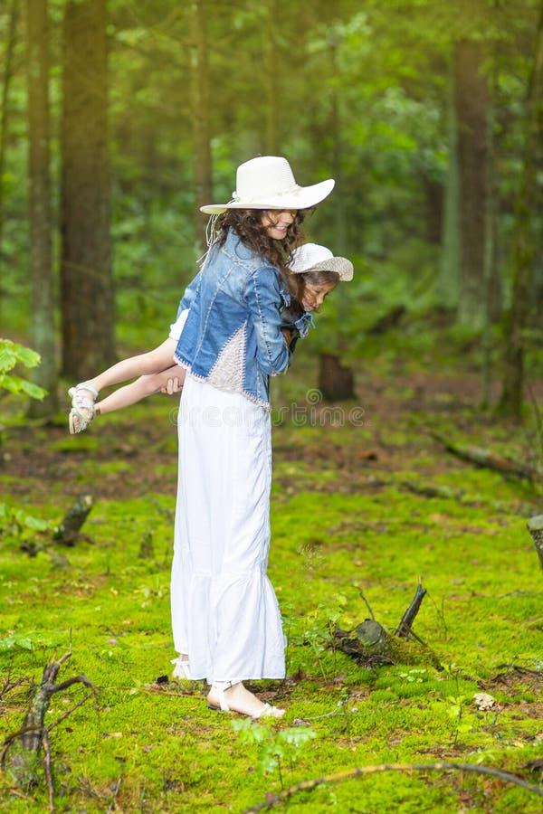 Positiva Caucasian par av modern och den lilla dottern som tillsammans spelar i grön sommarskog royaltyfri bild