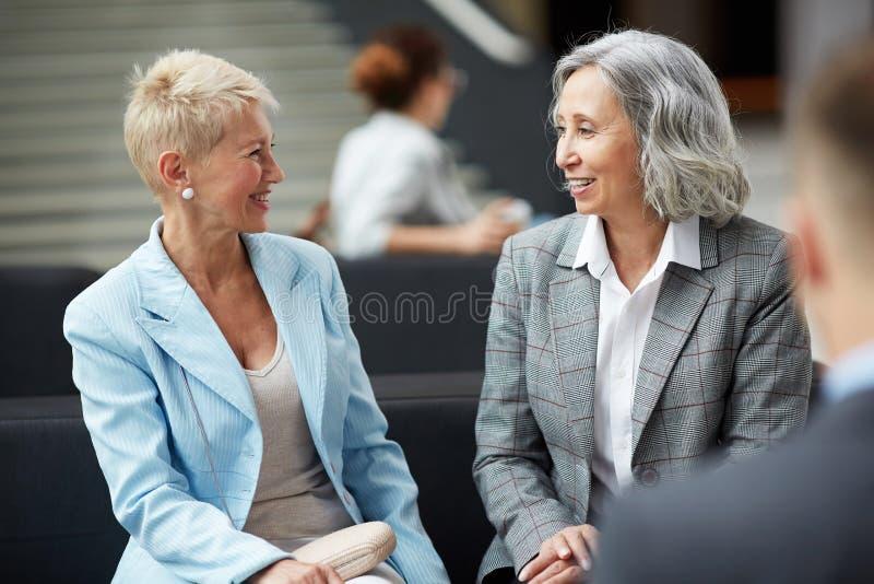 Positiva damer som talar i lobby royaltyfri bild