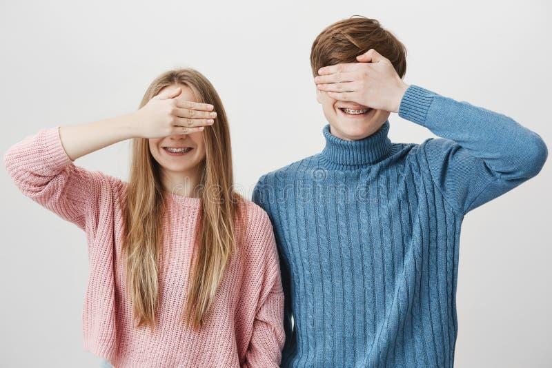 Positiva europeiska par i stack färgglade tröjor som poserar mot grå bakgrund Blond ung man och kvinnlig fotografering för bildbyråer