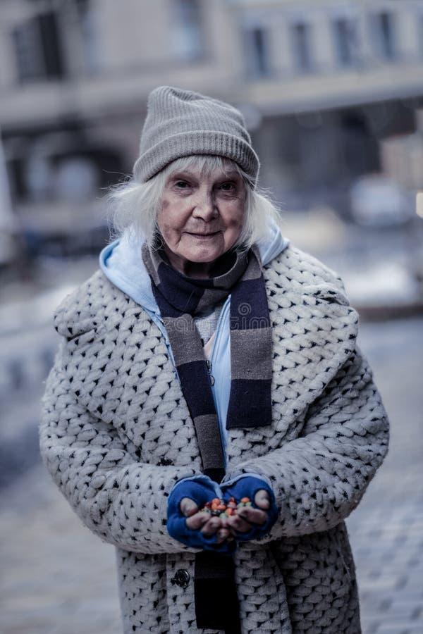 Positiva fattiga sötsaker för kvinnainnehavhandfull arkivfoto