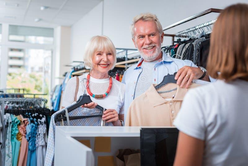 Positiva gråa haired kunder som är klara för betalningprocess royaltyfria foton