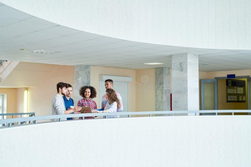 Positiva groupmates som diskuterar ämnen i korridor arkivfoton