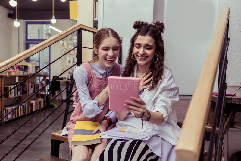 Positiva imponerade flickor som är lyckliga med resultat av deras inte professionell photoshoot royaltyfri bild