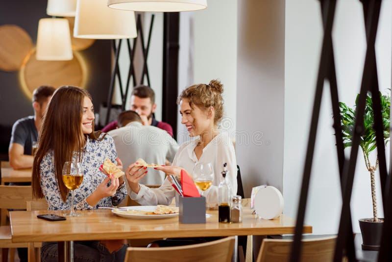 Positiva kvinnliga vänner som pratar och äter i pizzeria arkivbild