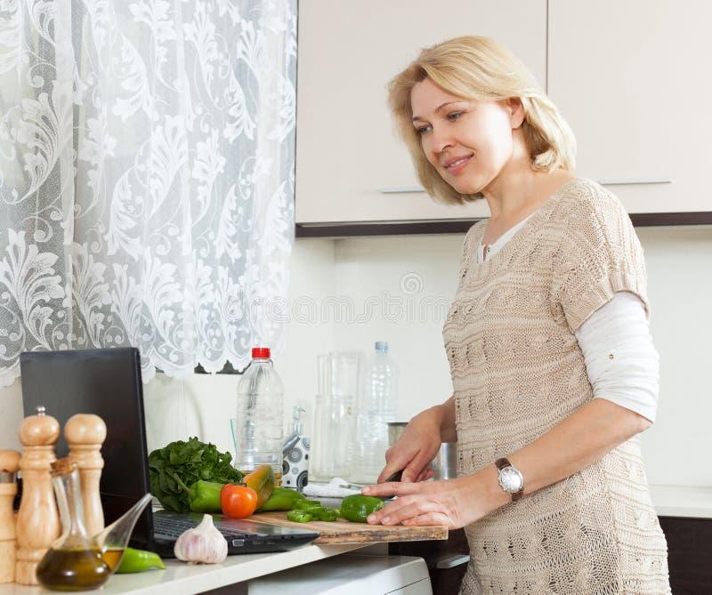 Positiva kvinnor som lagar mat med anteckningsboken royaltyfri bild