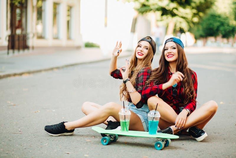 Positiva le par som sitter på gatan nära skateboarden royaltyfri foto