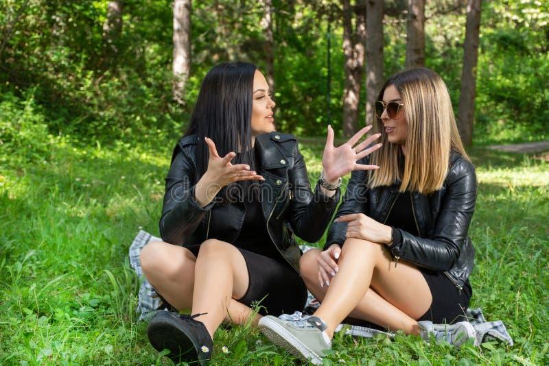 Positiva och lyckliga flickor som talar i natur och sitter i ängen på en filt, flickor skrattar och tycker om på en härlig vårdag royaltyfria foton