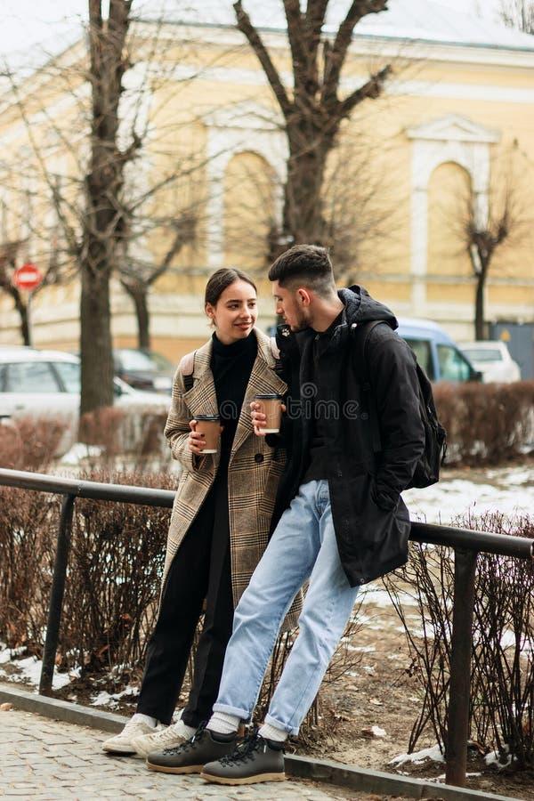 Positiva par som vilar efter, går, dricker takeaway coffe arkivbilder
