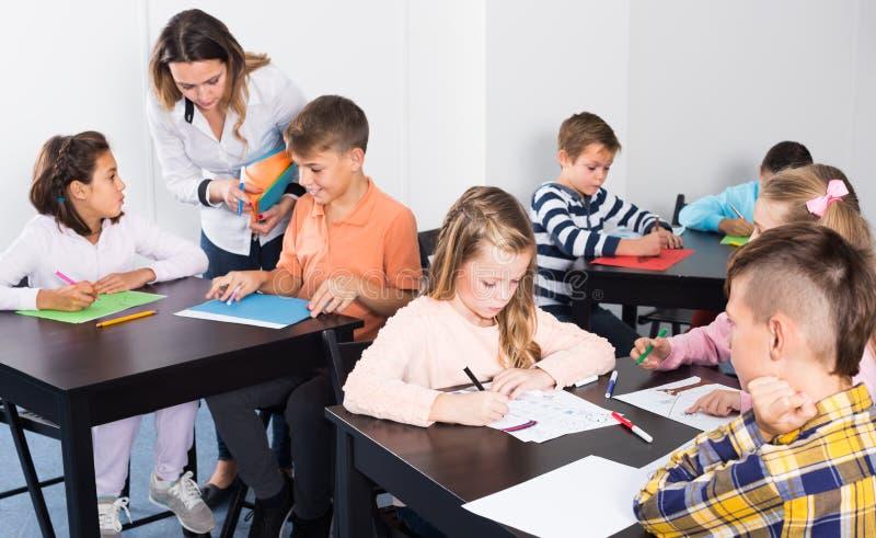 Positiva små barn med lärareteckningen i klassrum royaltyfri foto