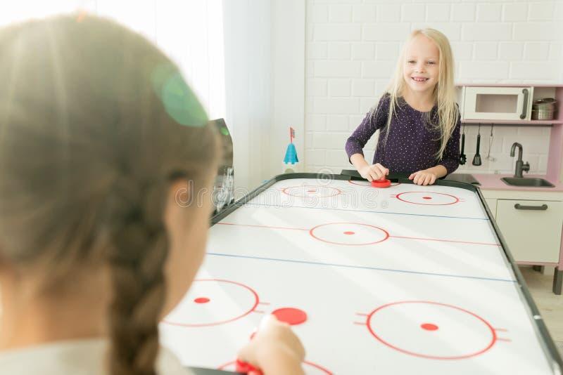Positiva små flickor som har gyckel i lekrum arkivfoto
