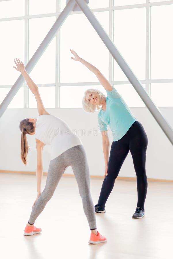 Positiva sportiga kvinnor som gör böjande övningar arkivbild