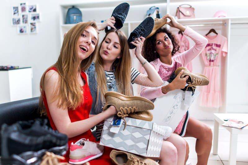 Positiva tonåriga flickvänner som har rolig tid tillsammans, medan göra shoppa att sitta välja nya skor som omkring bedrar och royaltyfria bilder