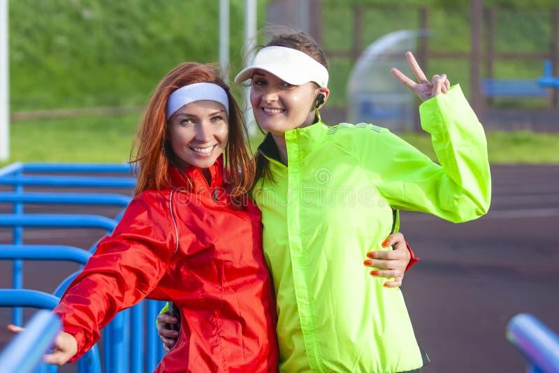 Positiva två och le Caucasian idrottskvinnor i den utomhus- dräkten som har bra Tid royaltyfria bilder