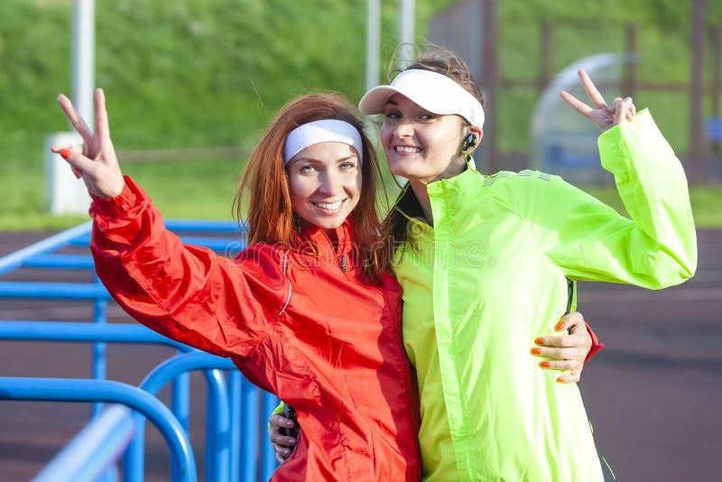 Positiva två och le Caucasian idrottskvinnor i utomhus- dräkt arkivbilder