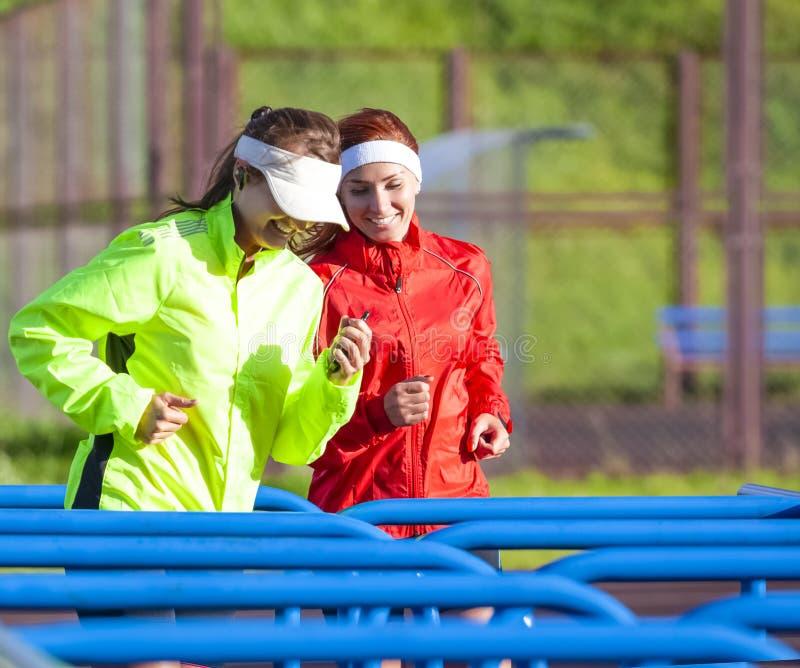 Positiva två och le Caucasian idrottskvinnor i utomhus- dräkt arkivfoto