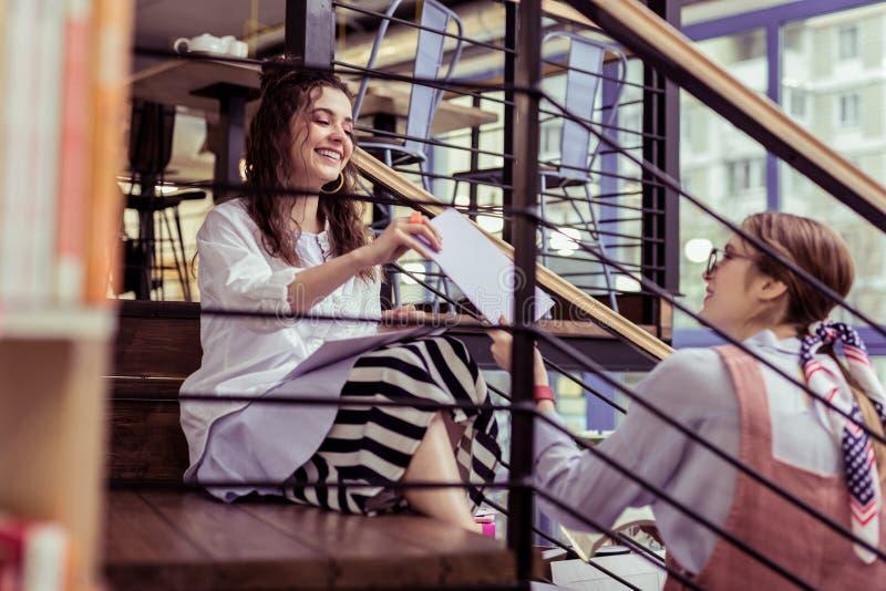 Positiva unga flickor som utbyter legitimationshandlingar, medan sitta på metalltrappa arkivfoton
