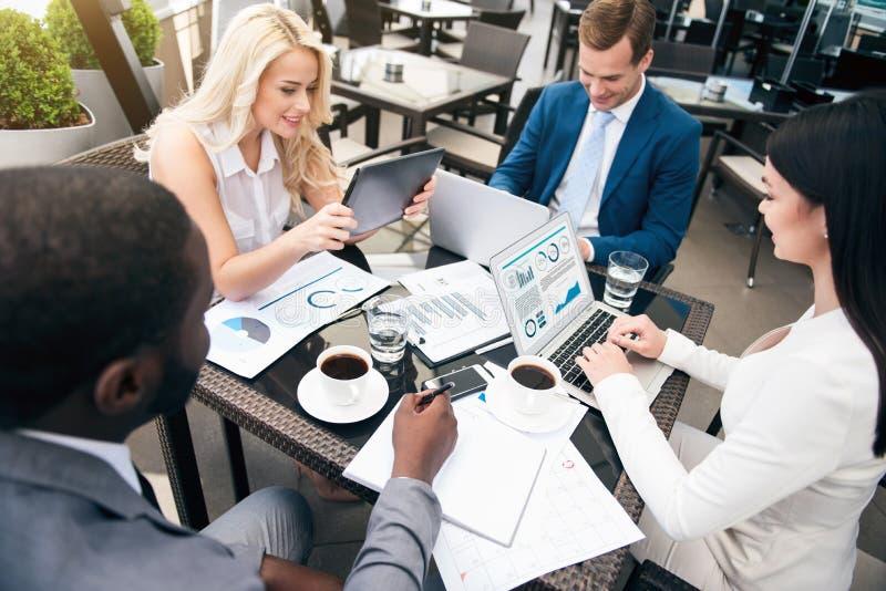 Positiva yrkesmässiga kollegor som sitter på tabellen arkivfoton