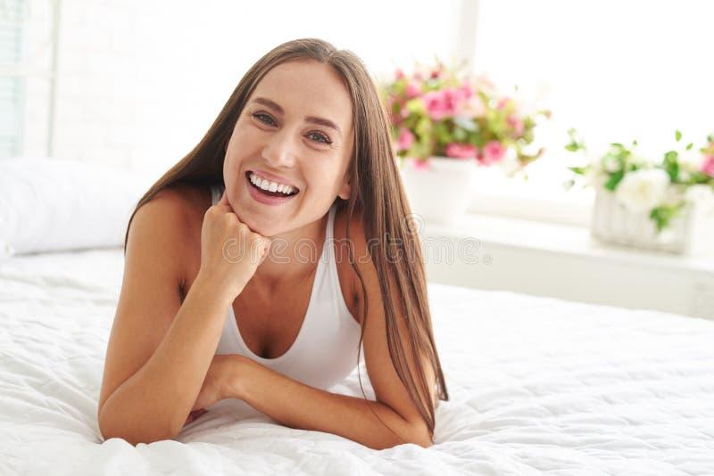 Positivamente sorrindo e relaxando fêmea inteiramente descansado na cama foto de stock royalty free