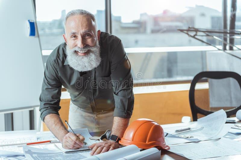 Positive ältere Arbeitskraft bearbeitet im Büro mit Lächeln stockbild