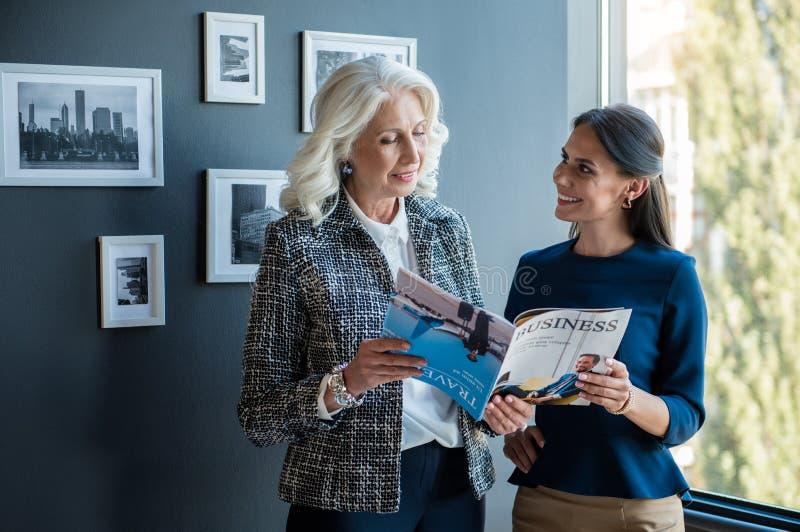 Positive ältere Dame und nettes Mädchen sind im Büro stockfotografie