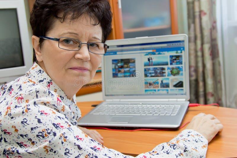 Positive ältere Frau, die am Notizbuch sitzt und Bilder auf Reise-Websites schaut stockbilder