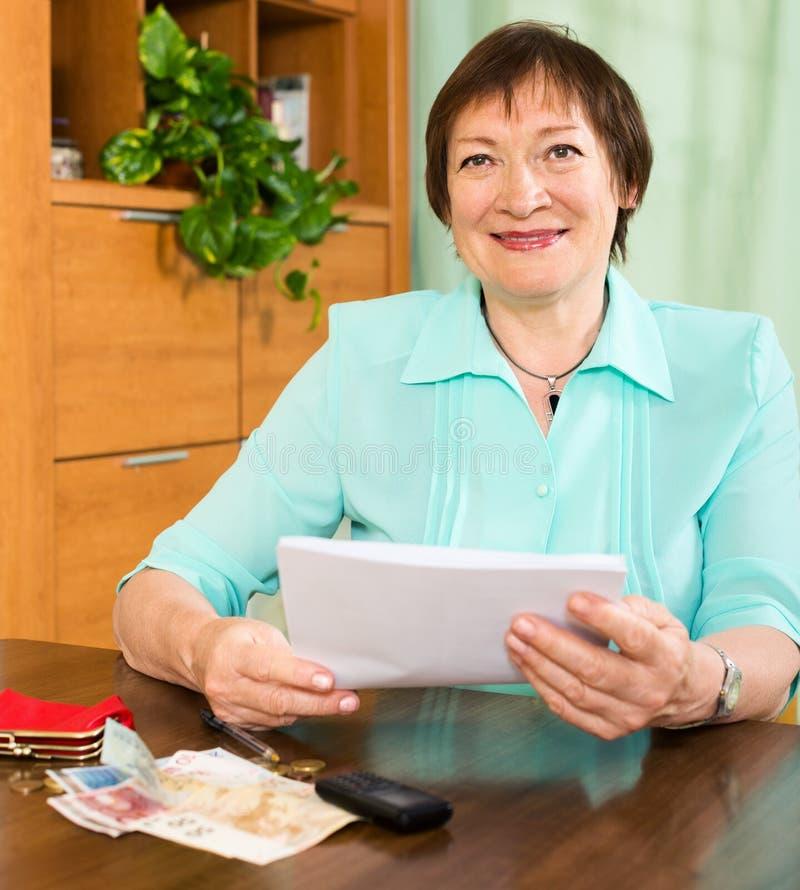 Positive ältere Frau mit Finanzdokumenten und Geld lizenzfreie stockbilder