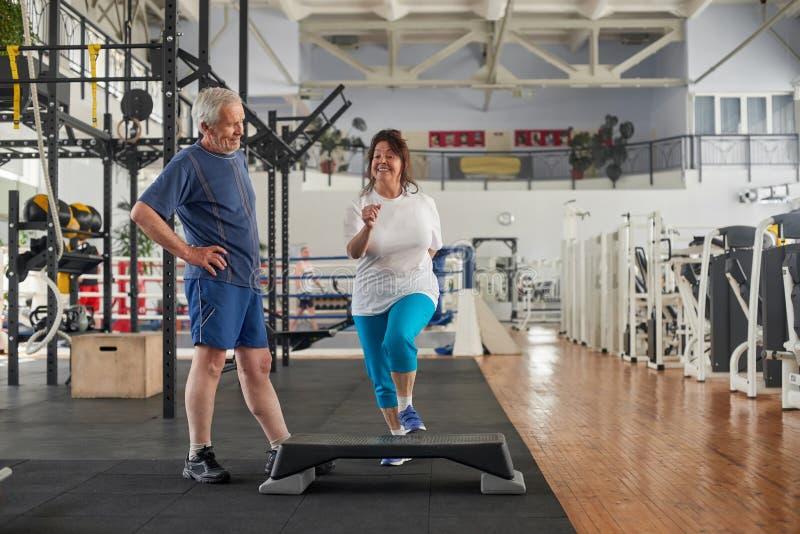 Positive ältere Paare, die an der Turnhalle trainieren lizenzfreie stockbilder