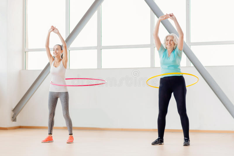 Positive active women rotating hula hoops. Developing waist. Positive active joyful women standing in the gym hall and rotating hula hoops while training royalty free stock photography