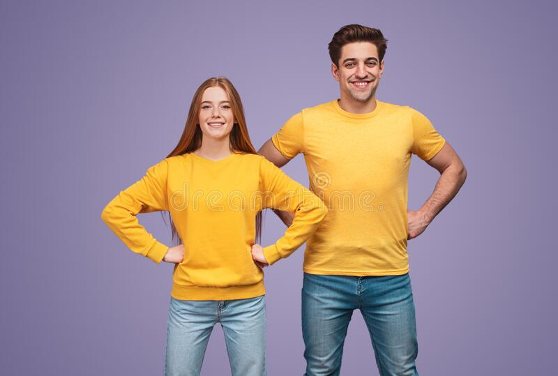 Positive active young couple in yellow shirts looking at camera royalty free stock photos