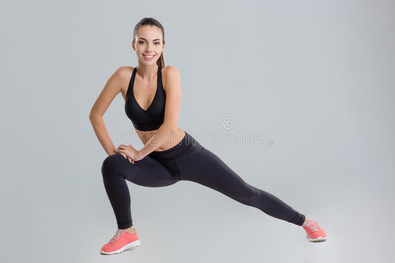 Positive active young fitness woman warming up and stretching stock photo