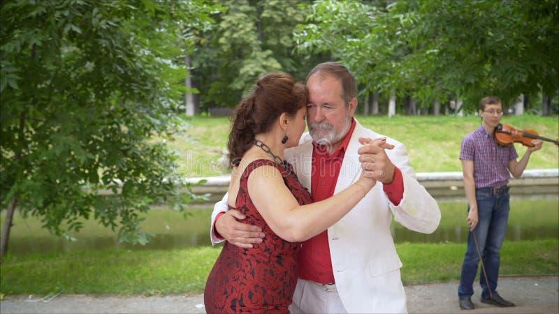 Positive adult friends dancing pair dance in garden. elderly couple dancing tango. Elderly man and woman dancing. Positive adult friends dancing pair dance in royalty free stock photos