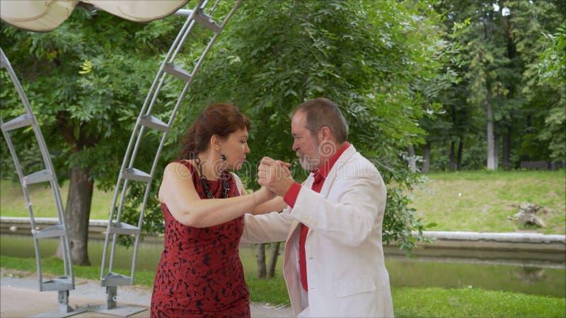 Positive adult friends dancing pair dance in garden. elderly couple dancing tango. Elderly man and woman dancing. Positive adult friends dancing pair dance in royalty free stock images