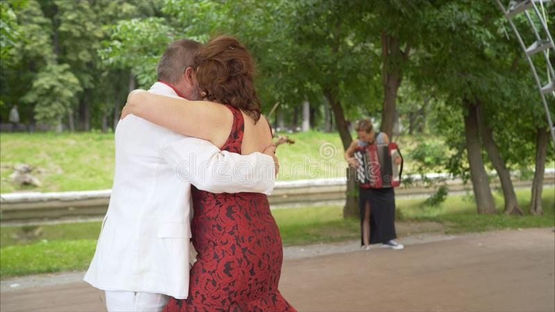 Positive adult friends dancing pair dance in garden. elderly couple dancing tango. Elderly man and woman dancing. Positive adult friends dancing pair dance in stock photos