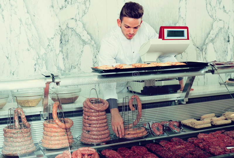 Download Positive Adult Man Seller Working At Meat Market Stock Photo - Image: 83701926