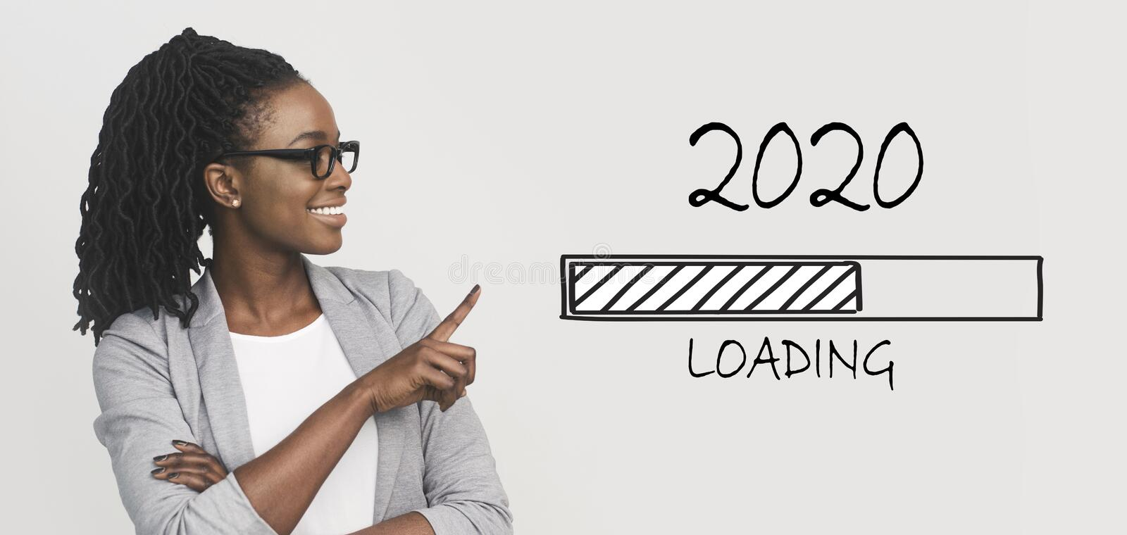 Positive african business woman pointing at 2020 loading bar. 2020 coming soon. Positive african business woman pointing at loading bar, panorama stock photography