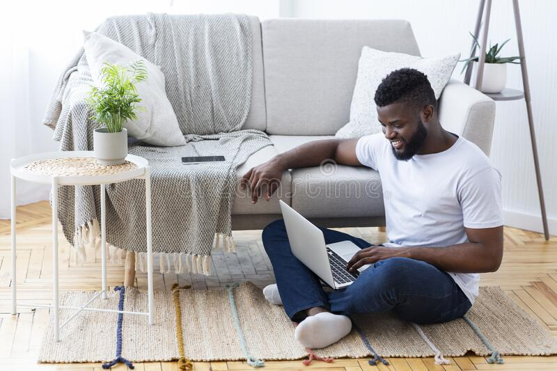 Positive african man surfing internet on laptop stock photography