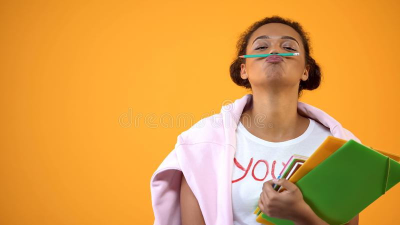 Positive african teenager holding pencil between nose and lips, mustache joke royalty free stock images
